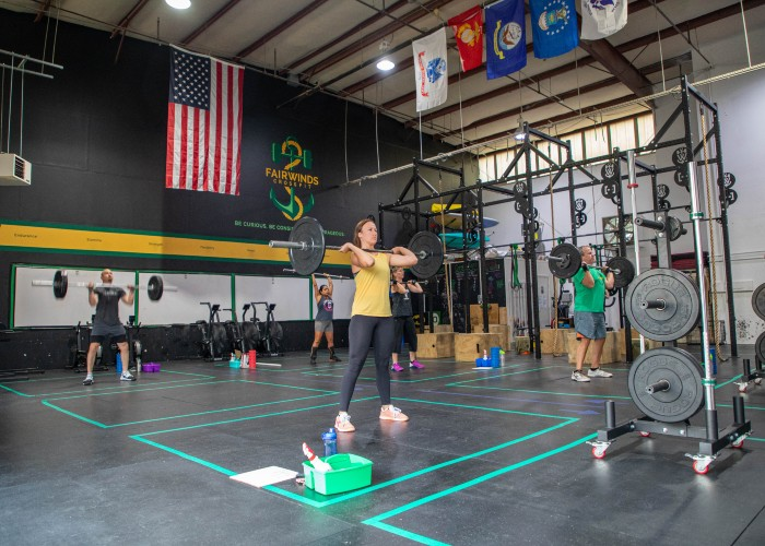 woman and man in group crossfit class lifting barbells